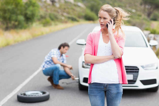 a woman on her phone while a man is fixing a tire on the background